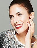 Lächelnde brünette Frau mit Hochsteckfrisur und Paillettenshirt, Lippen dunkelrot geschminkt, hält Hand an Gesicht