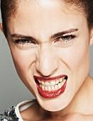 Brünette Frau in Paillettenshirt, Lippen dunkelrot geschminkt, zeigt die Zähne (Close Up)