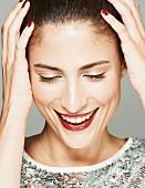 Lächelnde brünette Frau in Paillettenshirt, Lippen dunkelrot geschminkt, hält Hände an Kopf (Close Up)