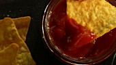 Tortilla chips being dipped in salsa