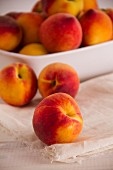 Fresh peaches on a cloth and in a bowl
