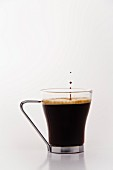 A glass of black coffee with droplets
