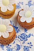 Flower decorations on chocolate and cappuccino macaroons on a blue-and-white paper cloth