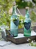Bottles of homemade woodruff syrup as a gift decorated with hearts and wreaths