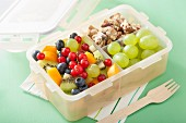 A lunch box with fruit salad and nut bars