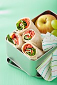 Ham and pepper wraps and fruit in a lunch box