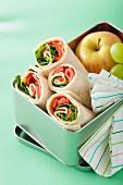 Schinken-Paprika-Wraps und Obst in einer Lunchbox