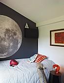 Ausschnitt eines Einzelbettes mit hellgrauem Plaid, vor dunkelgrau getönter Wand mit Abbildung eines Planeten im Jugendzimmer