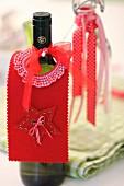 Selbstgebastelte, weihnachtliche Flaschenmanschette aus rotem Filz als Tropfenfänger für Weinflasche