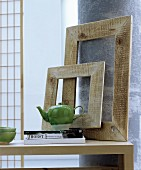 Fernöstliche Dekoideen: Schlichte Holzbilderrahmen auf Tisch an Säule gelehnt