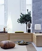 Wohnraum im asiatischen Stil mit niedrigen Holzschränken und Sitzgelegenheit aus Holz