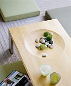 Wohnen im fernöstlichen Stil: Heller Holztisch mit Naturdeko in eingearbeiteter Vertiefung