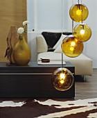Goldfarbene Kugel-Hängeleuchte in Wohnraum mit Tierfellteppich, Ablagetisch und modernem Recamiere