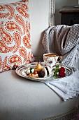 Tasse Tee mit Kleingebäck & pikanten Häppchen auf Silbertablett auf antikem Posterstuhl