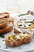 Baked cheese with rosemary and garlic on baguette slices