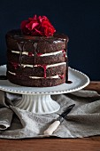 A chocolate cake with raspberry jam, chocolate glaze and rose petals