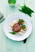 Minced meat steak Pojarski on asparagus with a wild garlic sauce