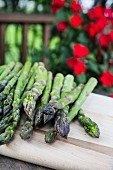 Green asparagus on a chopping board with red flowers in the background