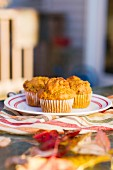 Vegane Kürbismuffins auf herbstlich gedecktem Gartentisch