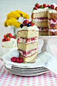 An Eton Mess layer cake with strawberries, raspberries and blueberries, sliced with a slice on a plate