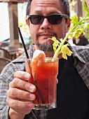 A man with a beard and sunglasses holding a Bloody Mary
