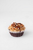 A chocolate cupcake with a caramel glaze and peanuts