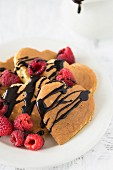 Heart-shaped pancakes with chocolate sauce and raspberries