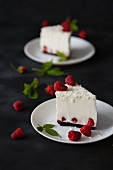 Two slices of coconut cheesecake with fresh raspberries