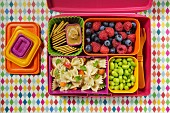Pasta salad, beans, berries and crackers in a lunchbox