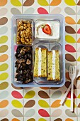 A sandwich, dried fruit, crunchy muesli and a yoghurt in a plastic box