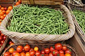 Green beans and tomatoes in woven baskets at a market