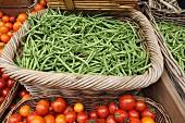 Grüne Bohnen und Tomaten in geflochtenen Körben auf dem Markt
