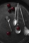 An arrangement of old silver spoons and bing cherries