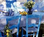 Blau lasierte Holzstühle vor Tisch mit weiss-blau karierter Tischdecke, in mediterranem Stil