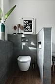 Separierter Toilettenbereich mit Hänge-WC an grau gefliester Wand