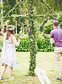 Young couple decorating garden for midsummer festival
