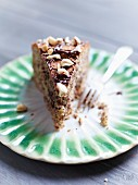 A slice of nut cake with chocolate drizzle