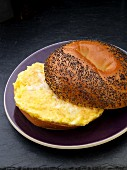 Scrambled egg on a poppy seed roll for breakfast