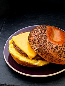 Sausage, egg and cheese breakfast sandwich on a poppy seed bagel