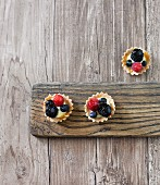 Organic mini berry tartlets on a wooden board
