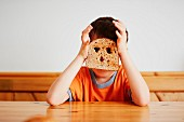 A boy holding a slice of toast in front of his face