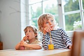 Two children sitting at a table drinking smoothies through straws