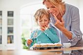 Mutter und Sohn bestäuben Muffins mit Puderzucker & naschen dabei