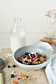 A bowl of muesli with fresh berries and a bottle of milk