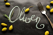 Scattered olives and a fork around the work 'Oliven'
