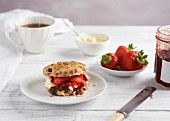 A scone with clotted cream, strawberries and jam served with tea