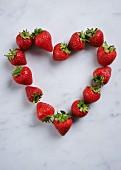 Ein Herz aus frischen Erdbeeren vor weißem Hintergrund