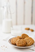 Oat biscuits on a plate with a glass and a bottle of milk in the background