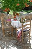 Gedeckter Tisch und Holzstühle in mediterranem Stil auf Terrasse