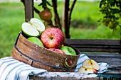 Rote & grüne Äpfel auf Tisch im Garten